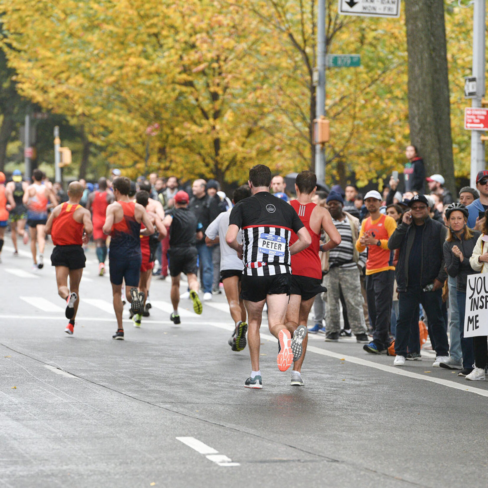 Runners pass cheering crowds lining a roadway in the Park