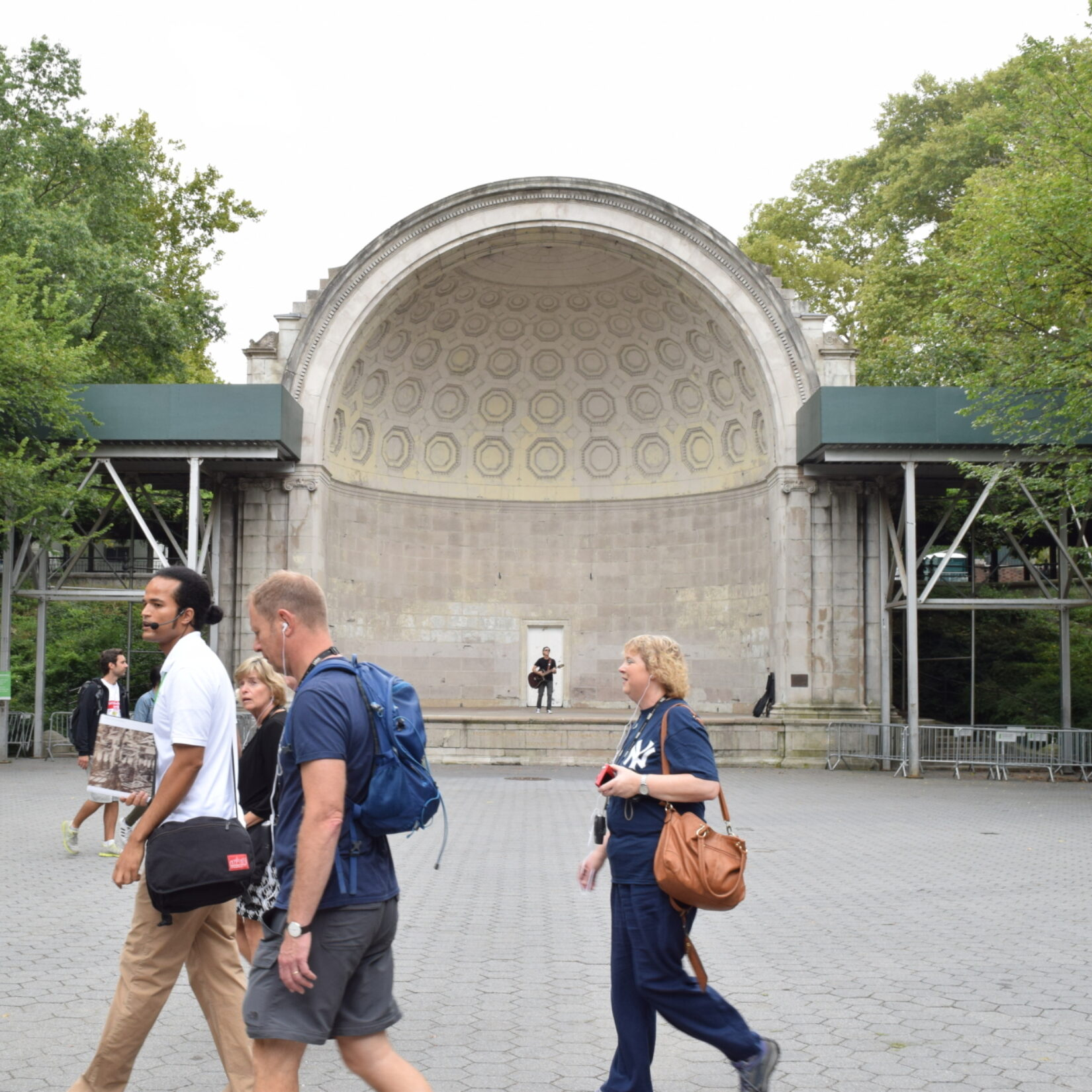 Park-goers pass a lone guitarist testing the acoustics of the bandshell.