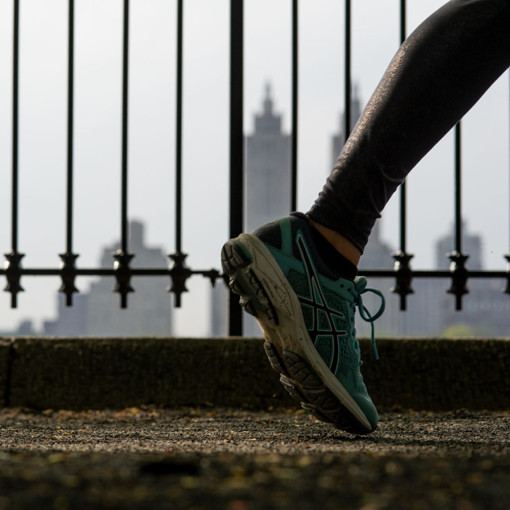 A close-up of a foot with the iron fence that surrounds the reservoir in the background
