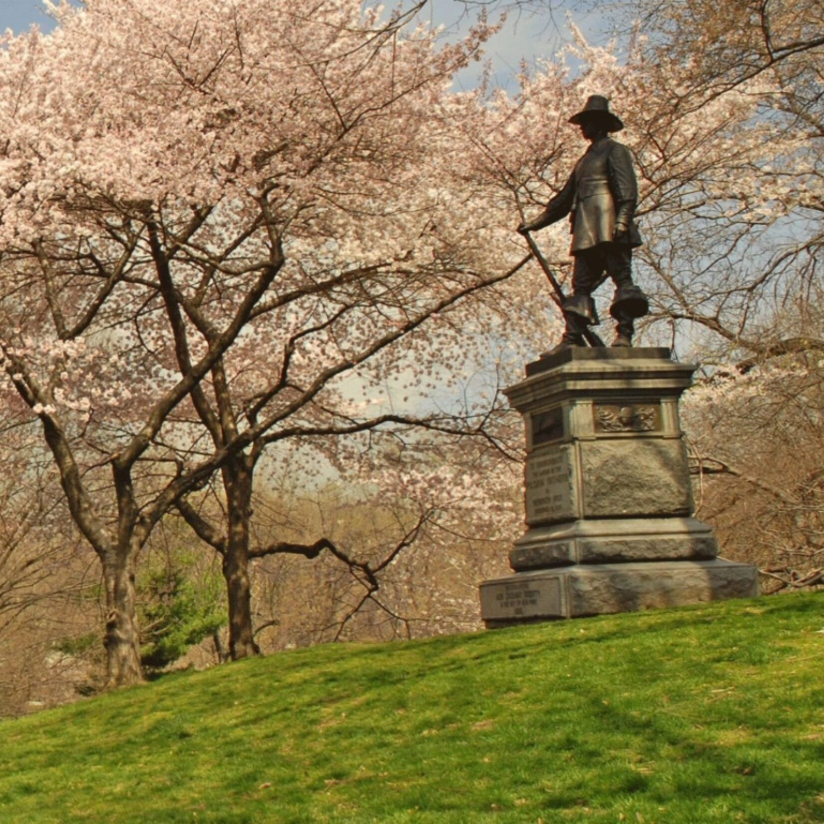 Trees sprouting pink, spring buds line the slope of the hill to the eponymous statue at the crest.