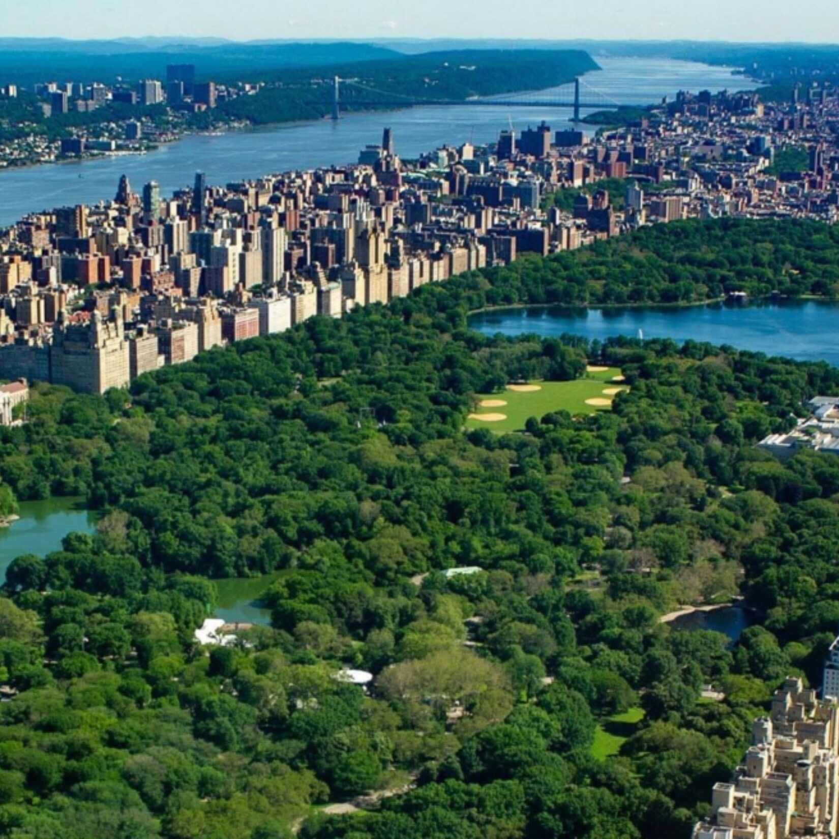 An aerial view of Central Park, looking north, with the West Side of Manhattan and the Hudson River.