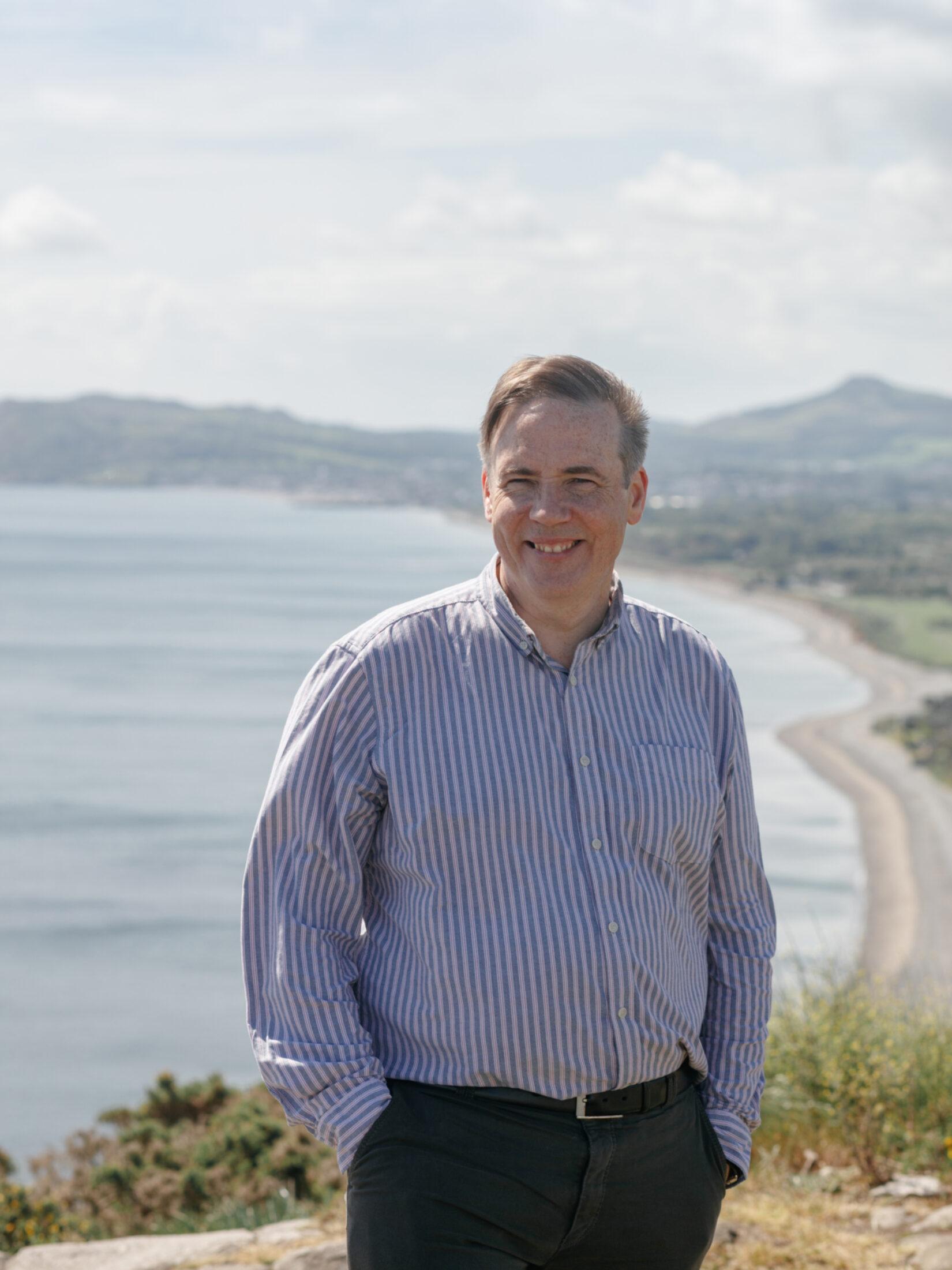 Portrait image of Shane O'Mara, photographed overlooking a beach