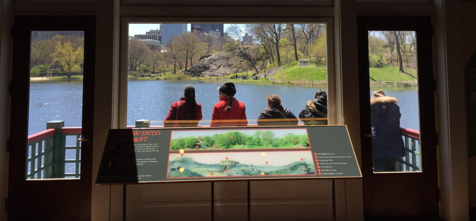 Part of the exhibit stands in front of a window, overlooking the landscape of the Harlem Meer it describes
