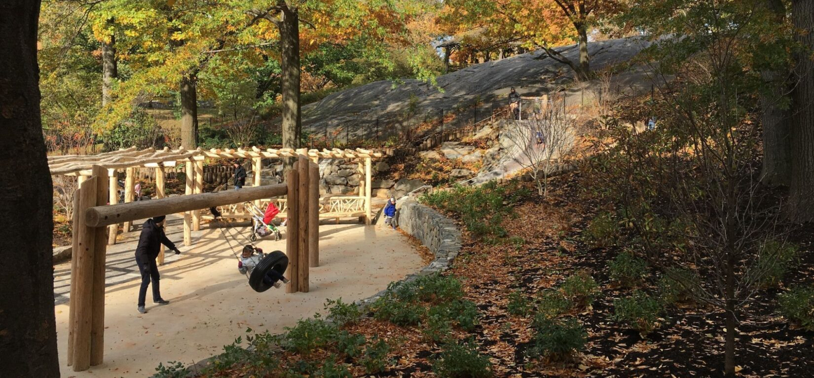 A parent and child enjoy the swing set of a playground surrounded by thick autumnal foliage