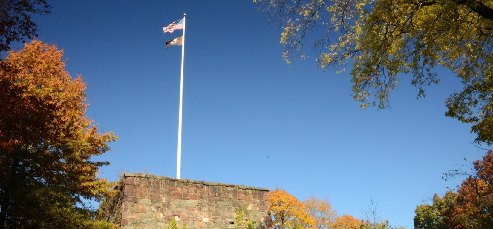 Two flags at the top of a white flagpole on the roof of the Blockhouse.