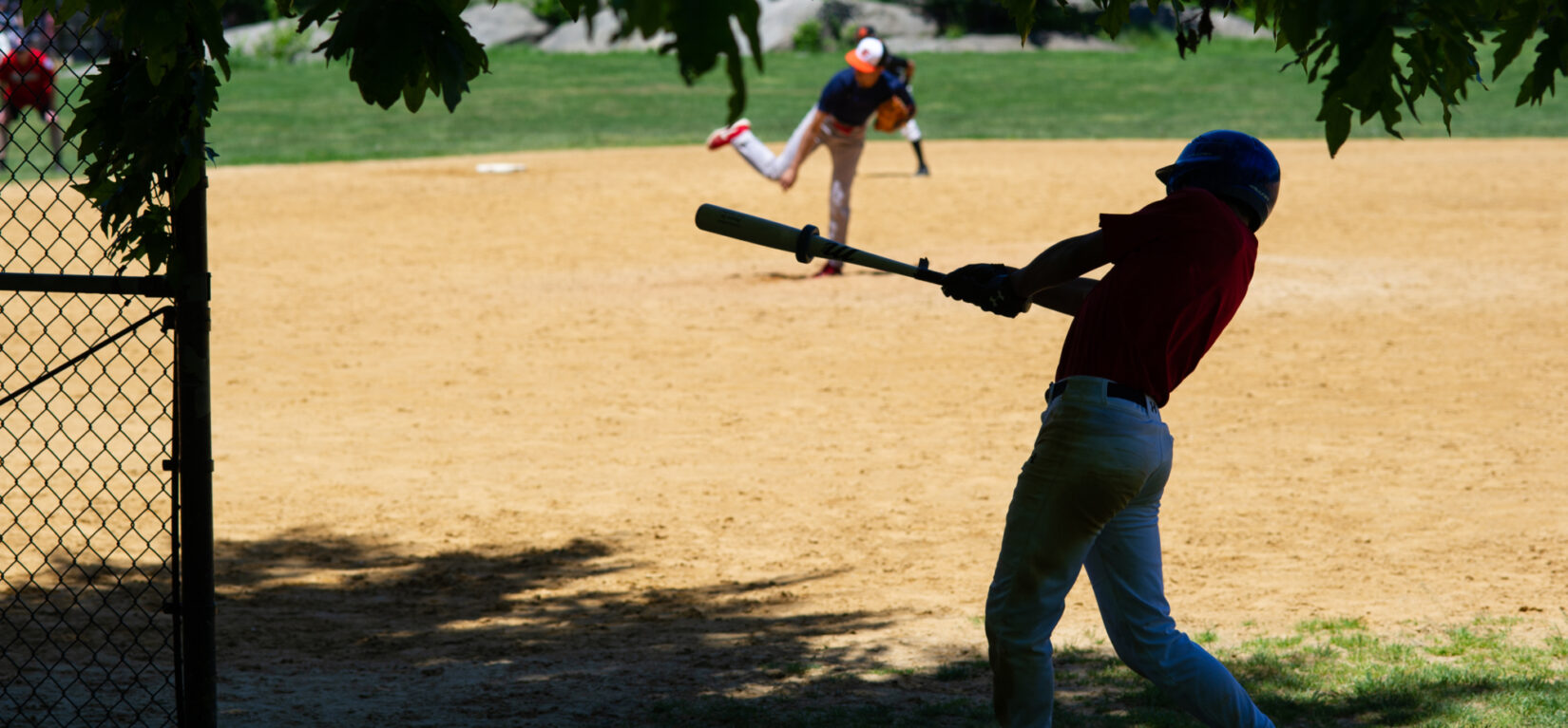 A younger player is on-deck, in the shade, ready for his at-bat