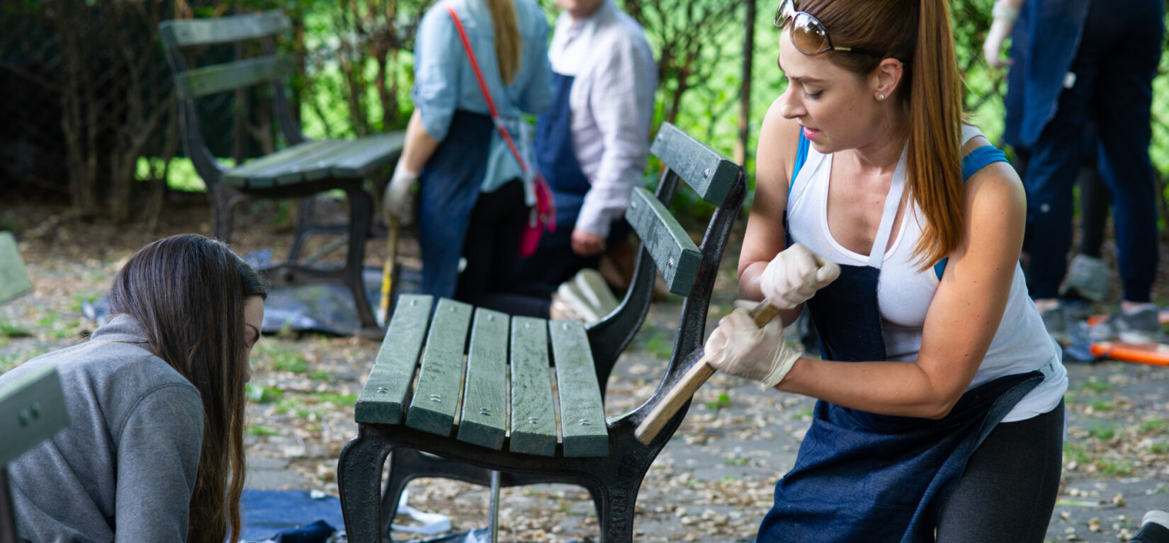Seasonal volunteers help out refurbishing park benches