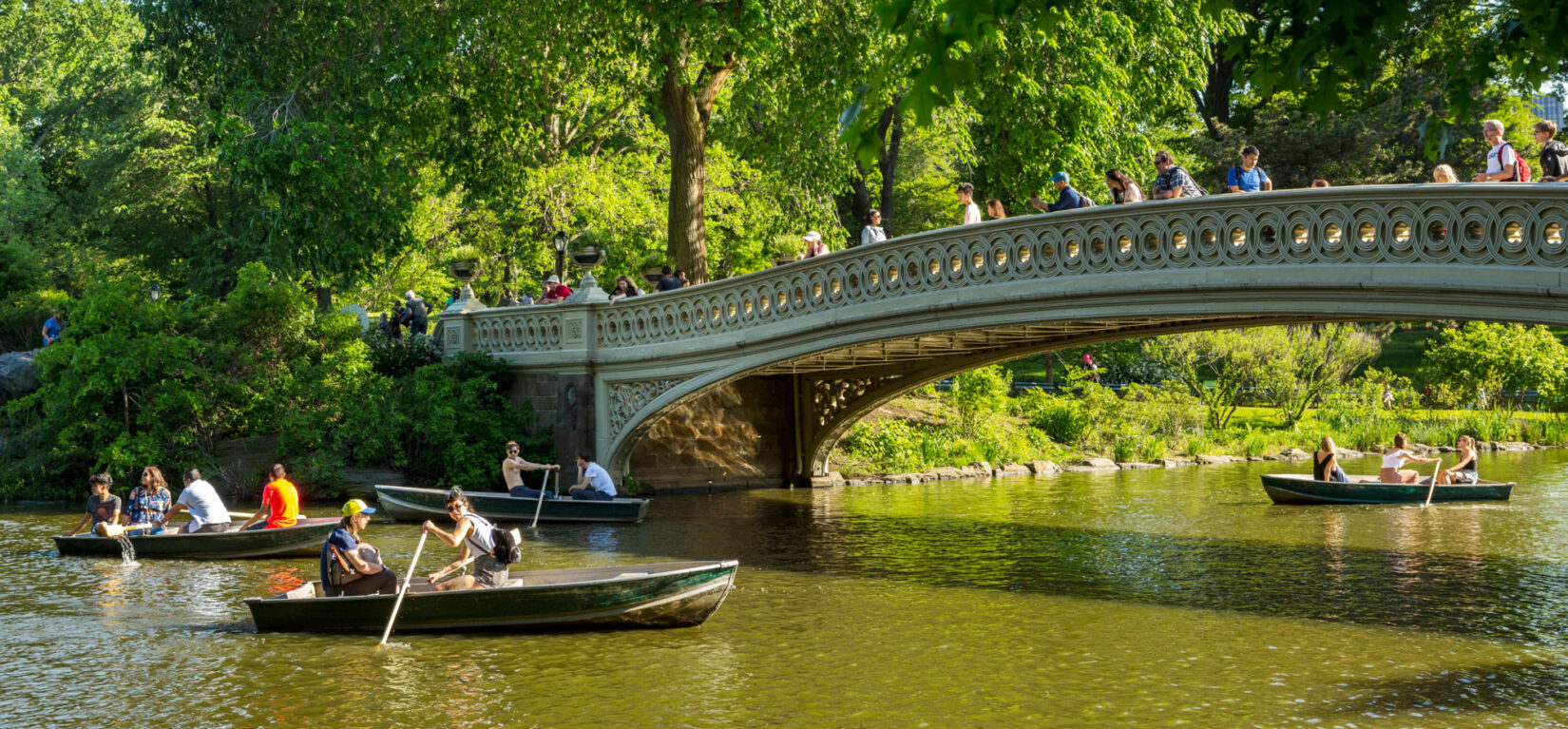 Boaters row beneath the span of the Bow Bridge
