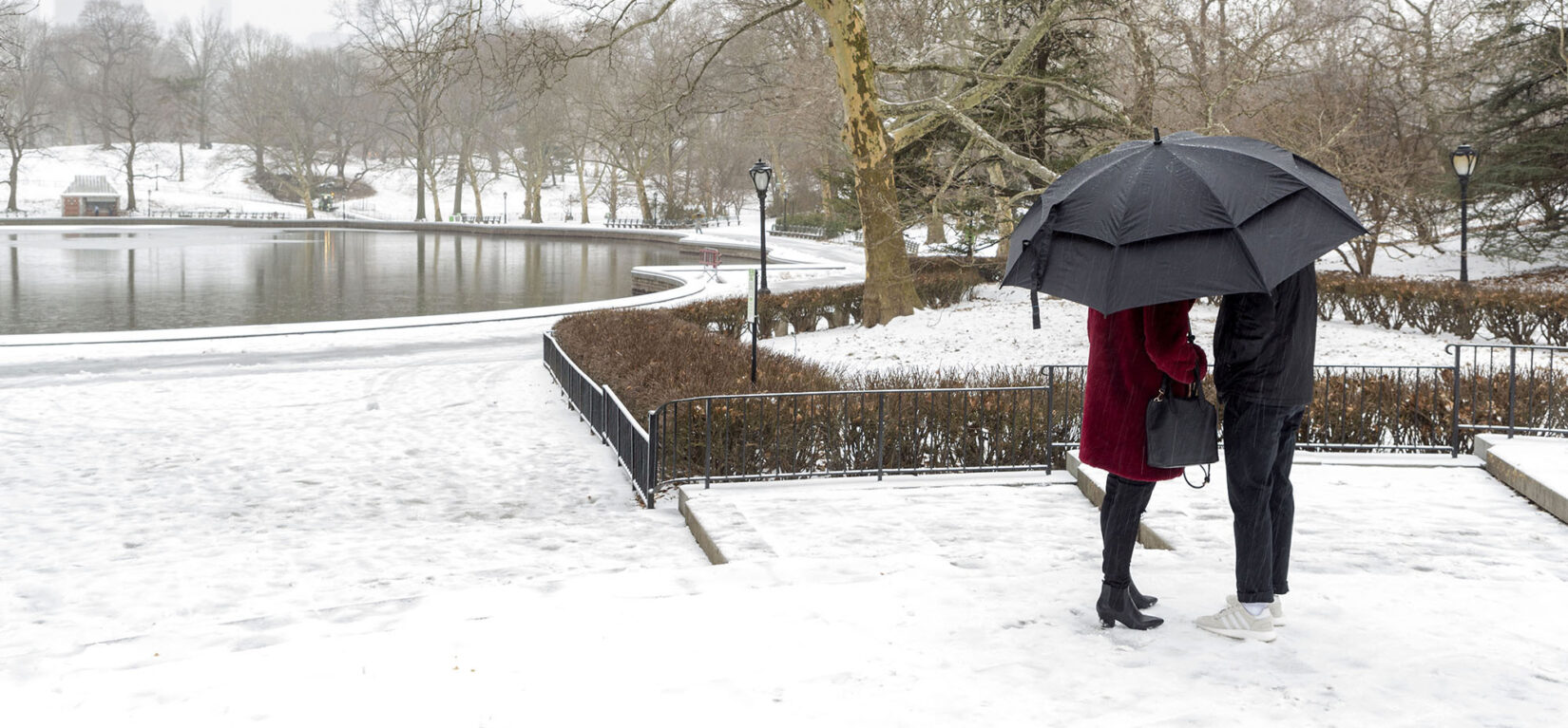 A couple huddle under an umbrella with the snow-covered Park surrounding Conservatory Water behind them