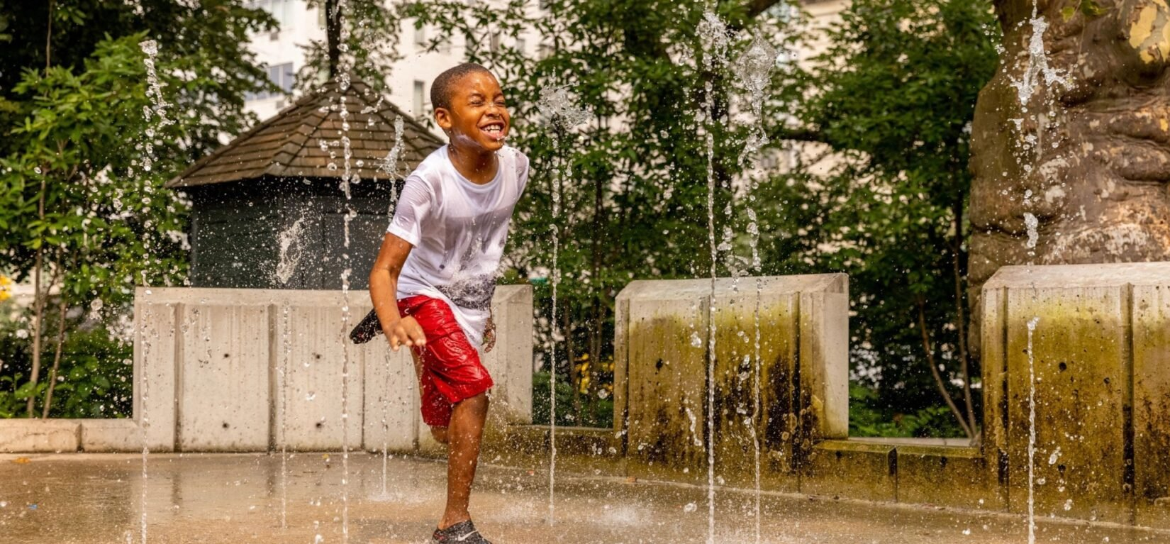 A young boy scrambles between water spouts in a Park playground.