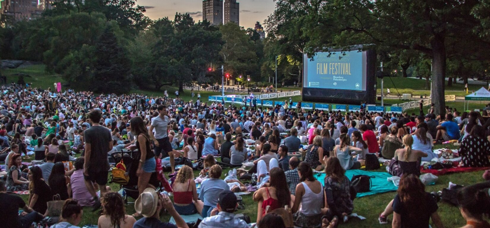 Hundreds of movie fans sit before a crowd-sized movie screen in the Sheep Medow at dusk.