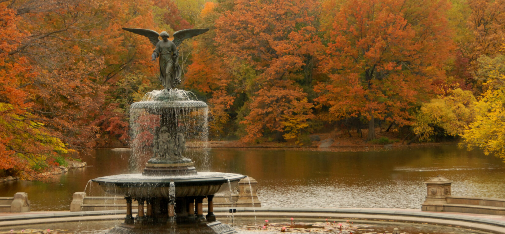 The Bethesda Fountain pictured in fall, with red and yellow foliage reflected in the Lake