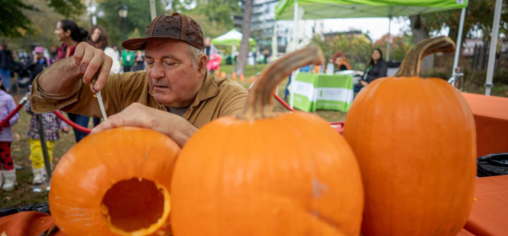 A Park staff member carving his way through a several pumpkins
