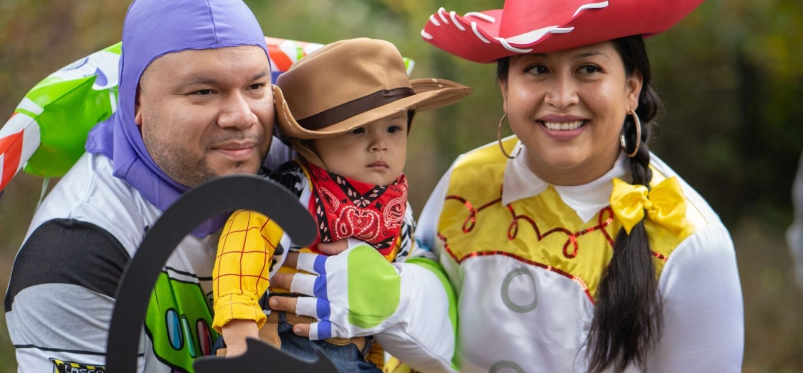 A young family pose in their coordinated Toy Story costumes