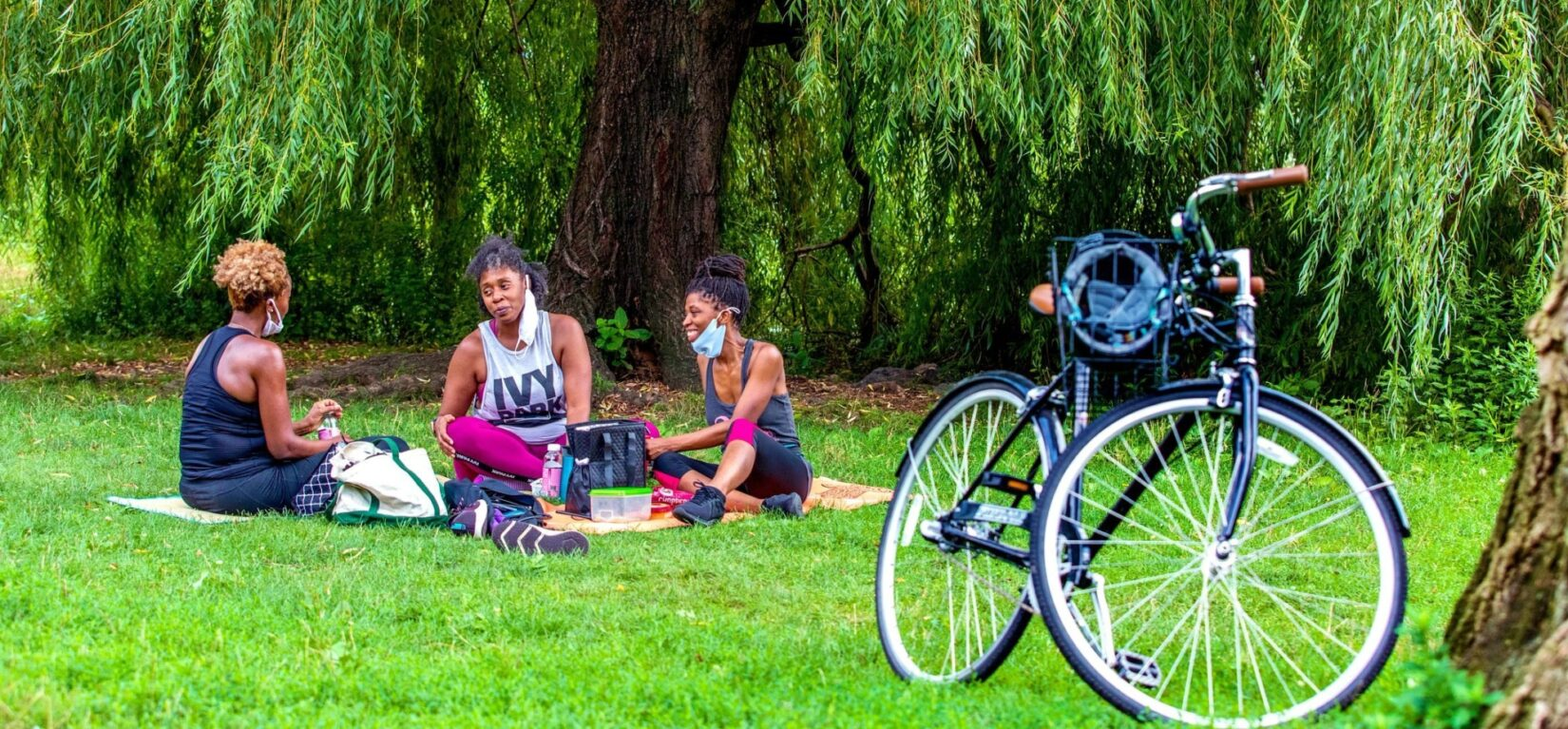 Three women enjoy a picnic on a blanket on Cedar Hill, with a parked bicycle in the foreground.