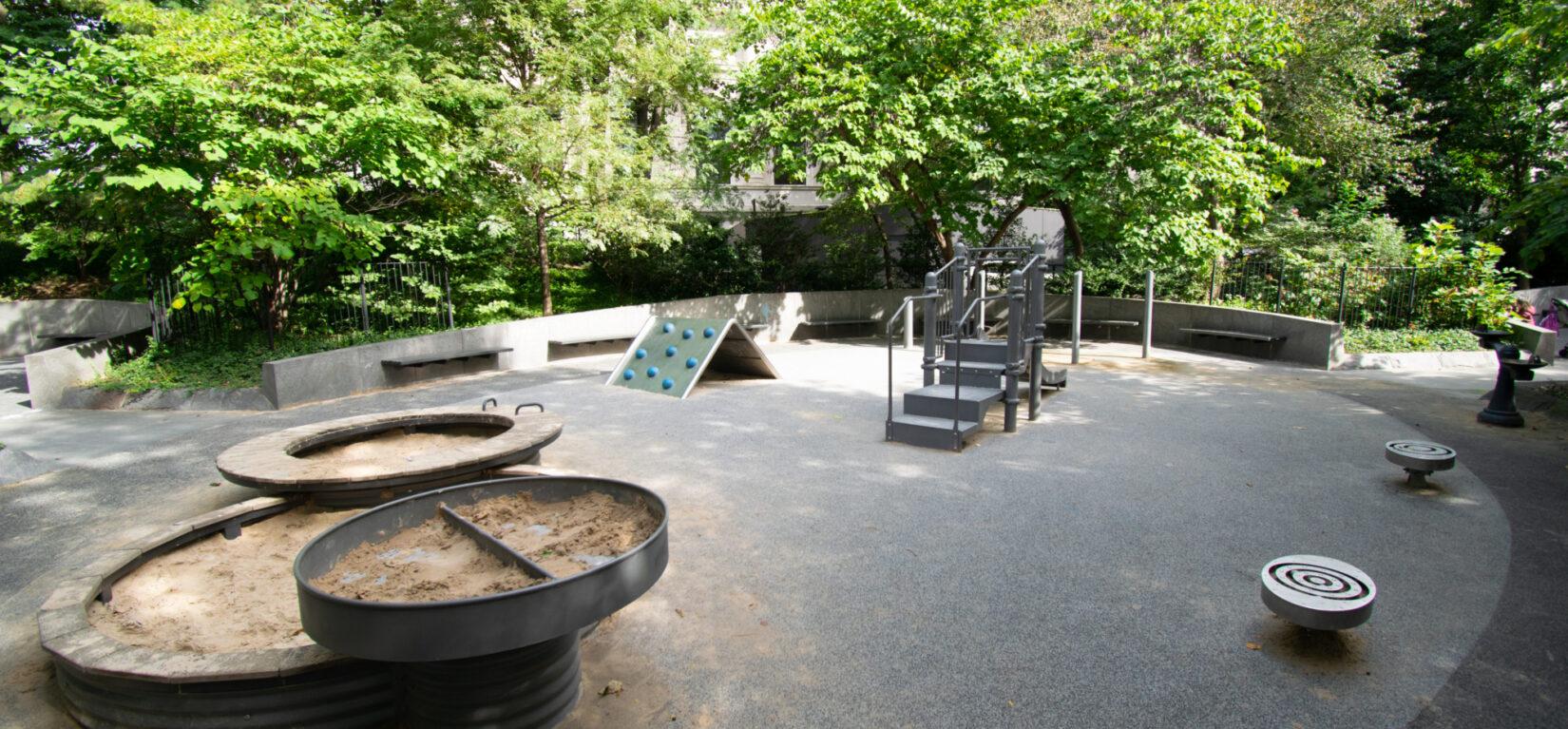 The circular play area features circular sandboxes and circular stools.