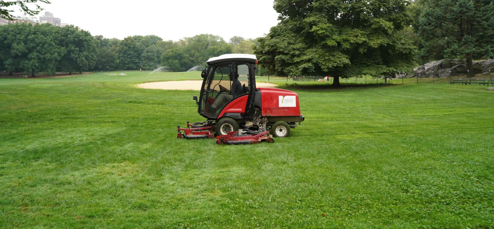 A riding mower trims a lawn near a ballfield