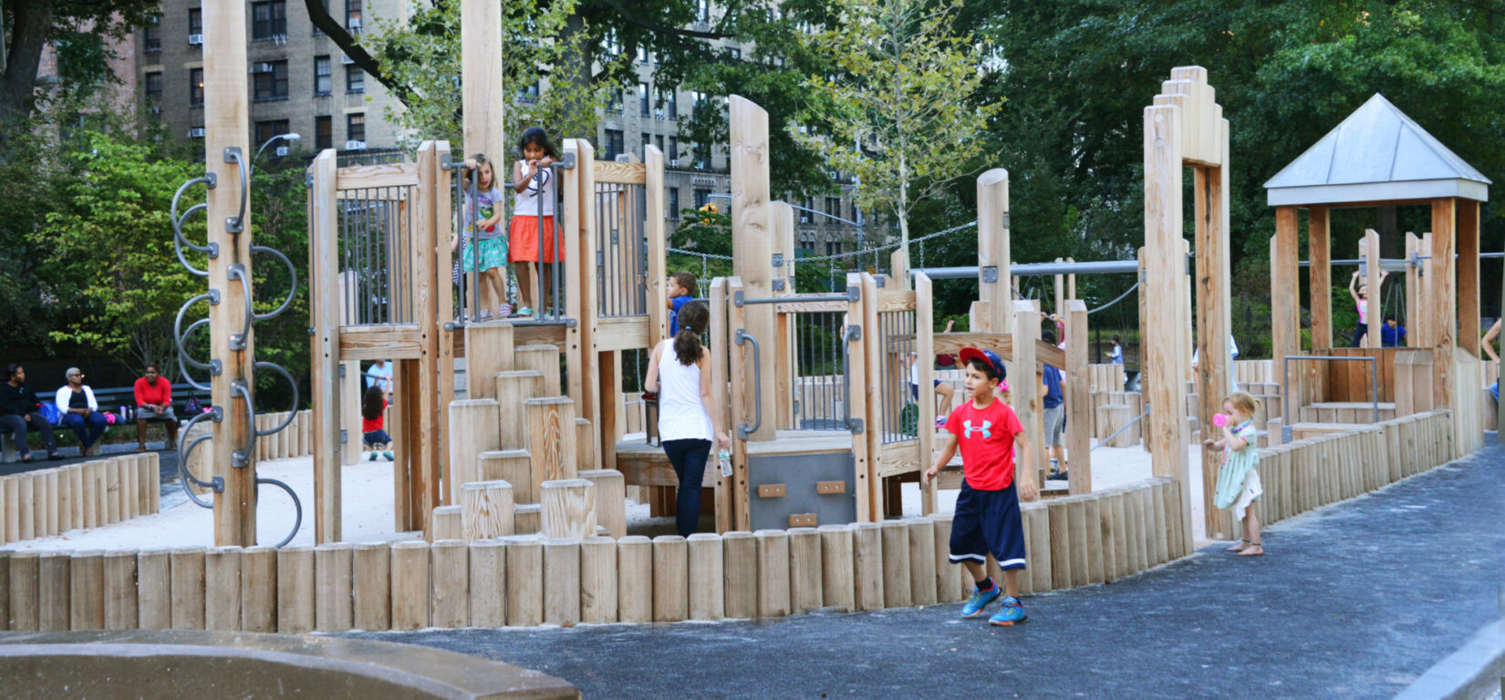 Wooden play structures surround sandy ground, surrounded by a path.