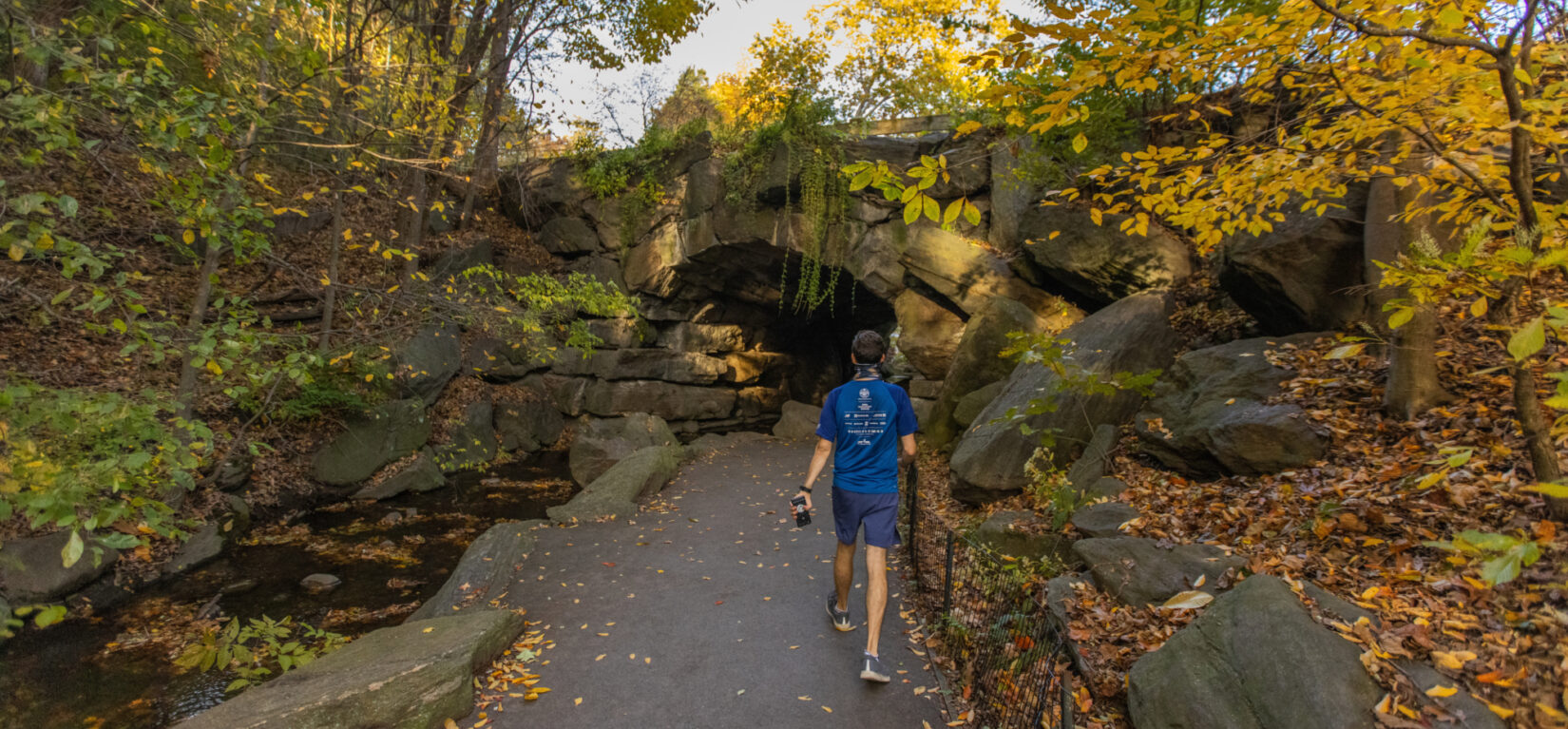 A hiker approaches the Huddlestone Arch in autumn