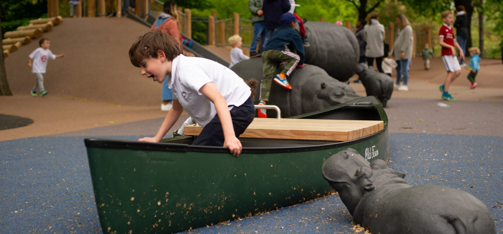 A young boy enjoys a boat-like feature of the playground