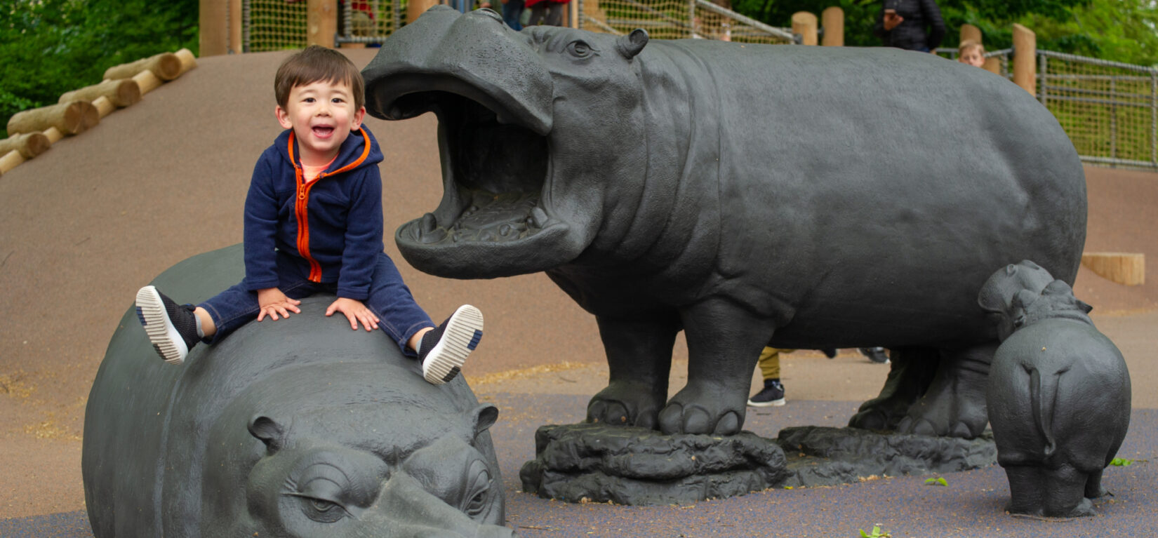 A small child sits atop one of the sculptures of a hippo in the playground.