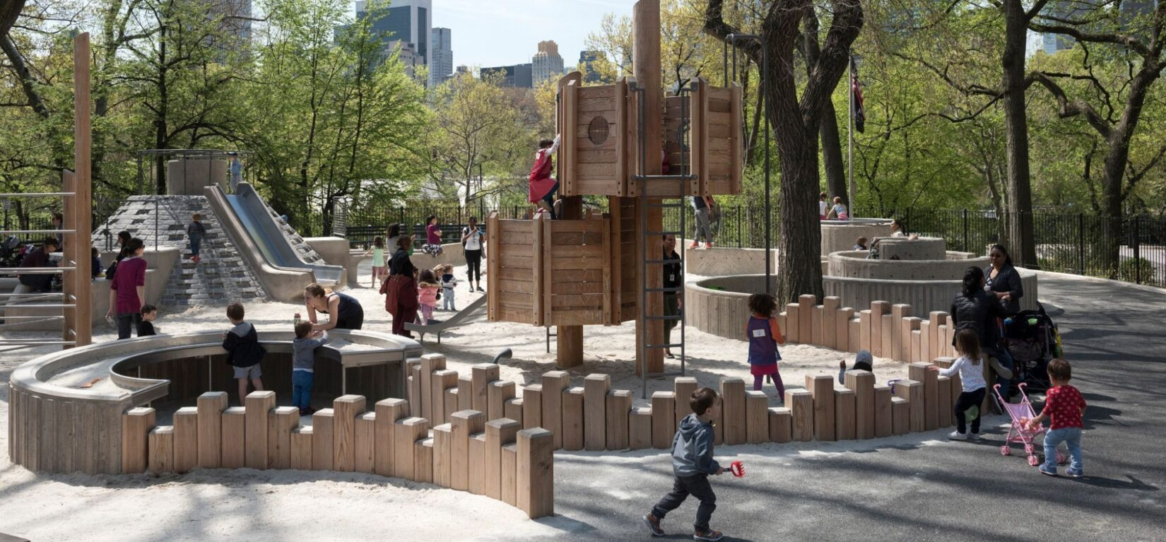 Children play late on an early spring day in a sand area ringed by vertical wooden beams of random heights.