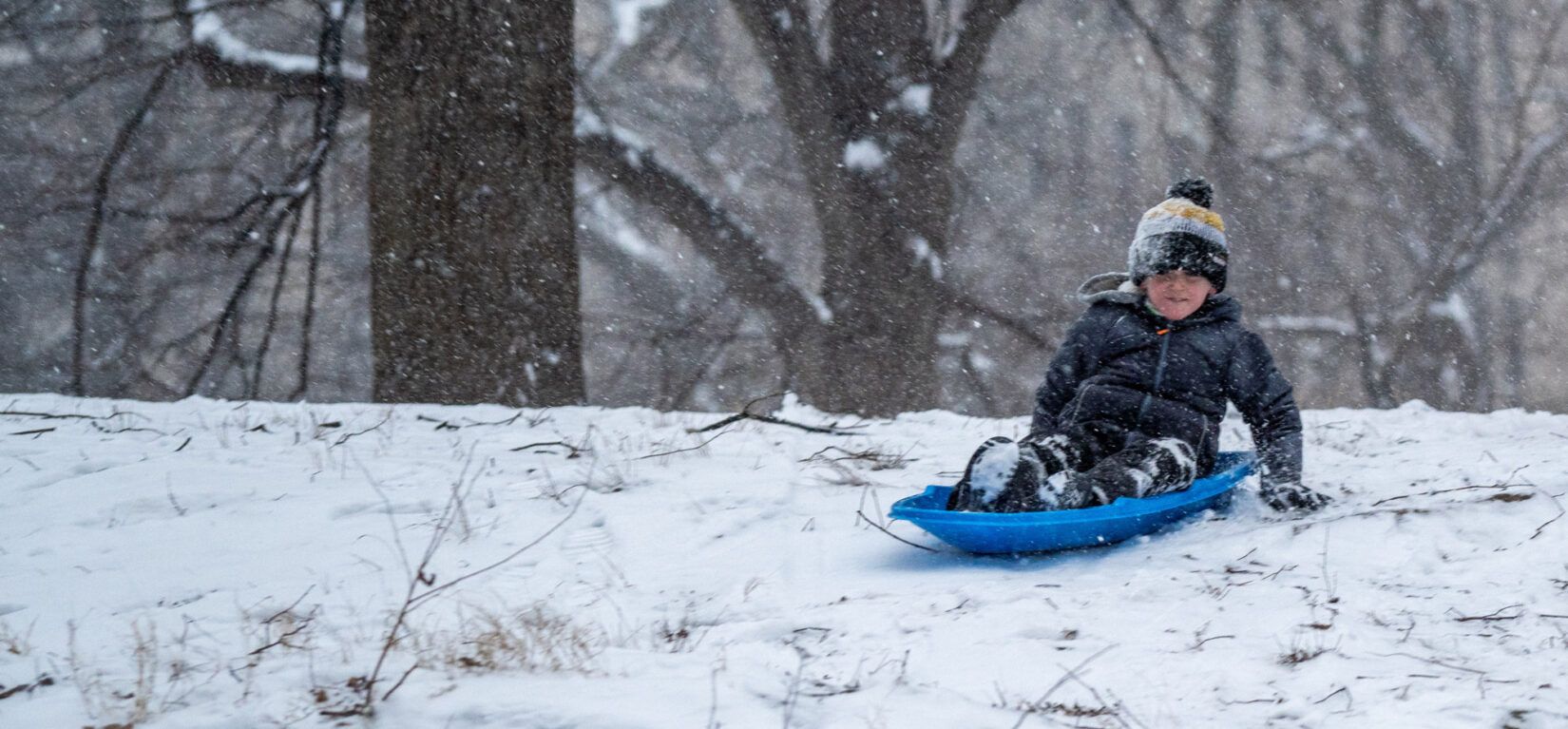 A boy on a blue sled in heavy snow