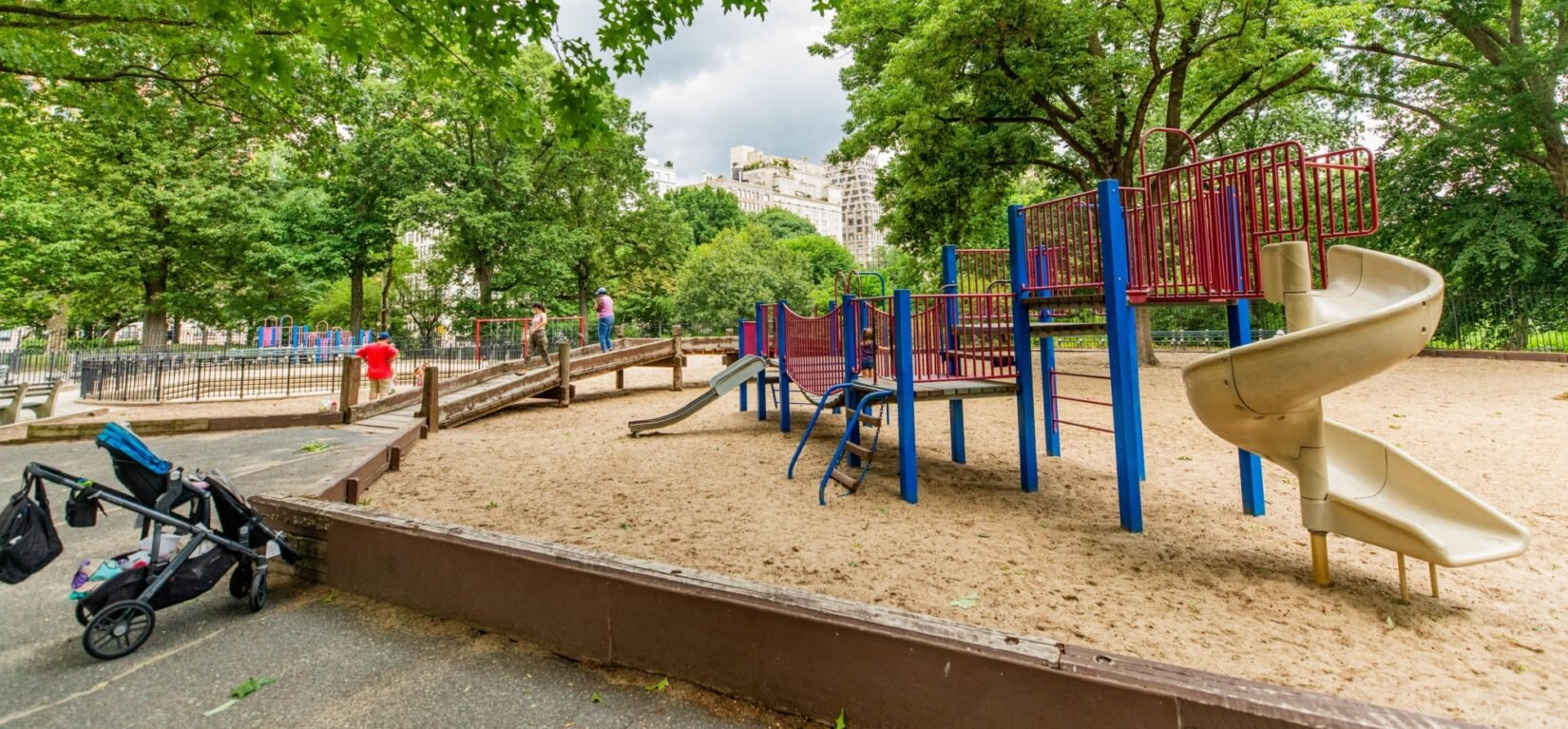 The climbing and sliding equipment in a large sandbox, seen in summer