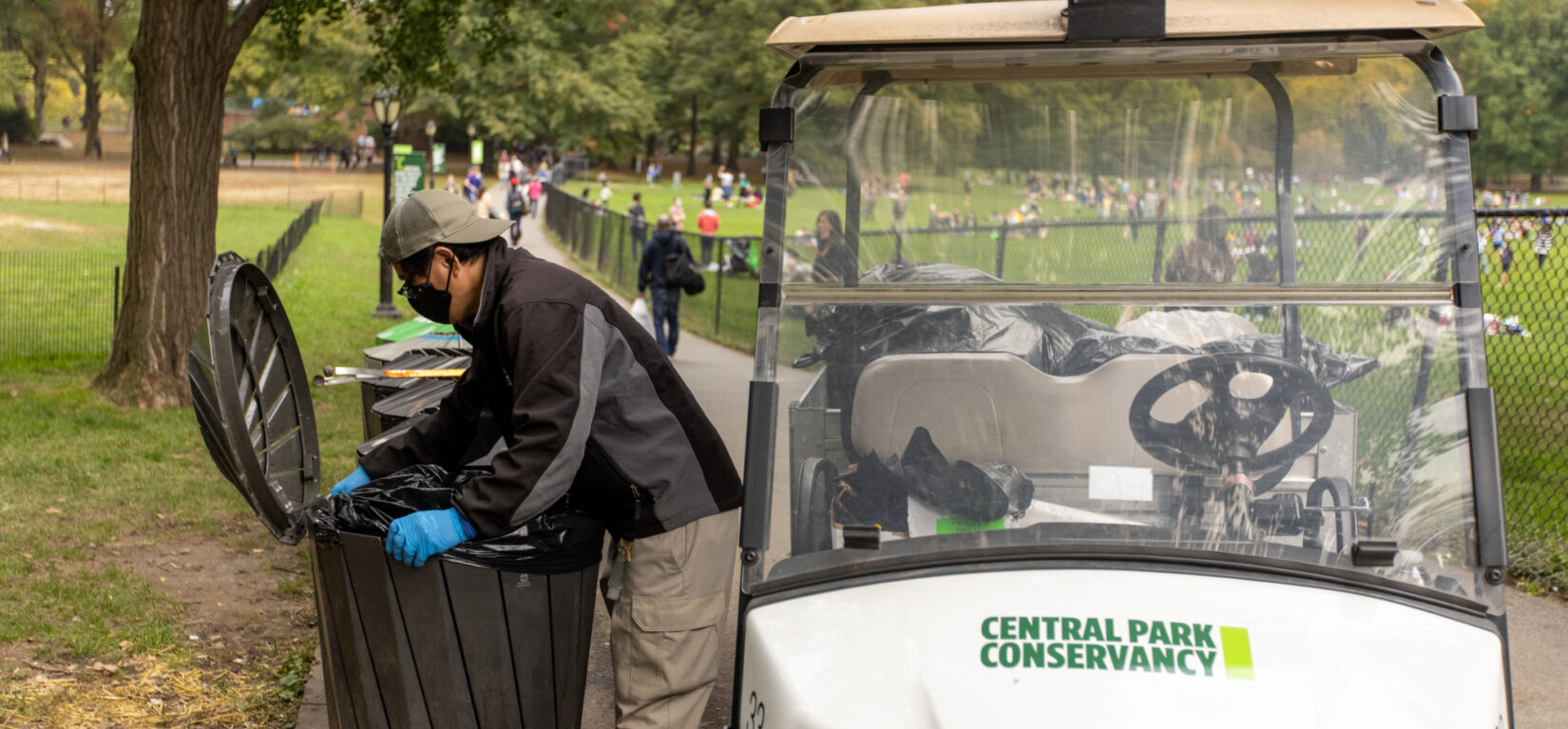 Staff member Danilo Maturan uses an electric cart as part of his trash maintenance routine.