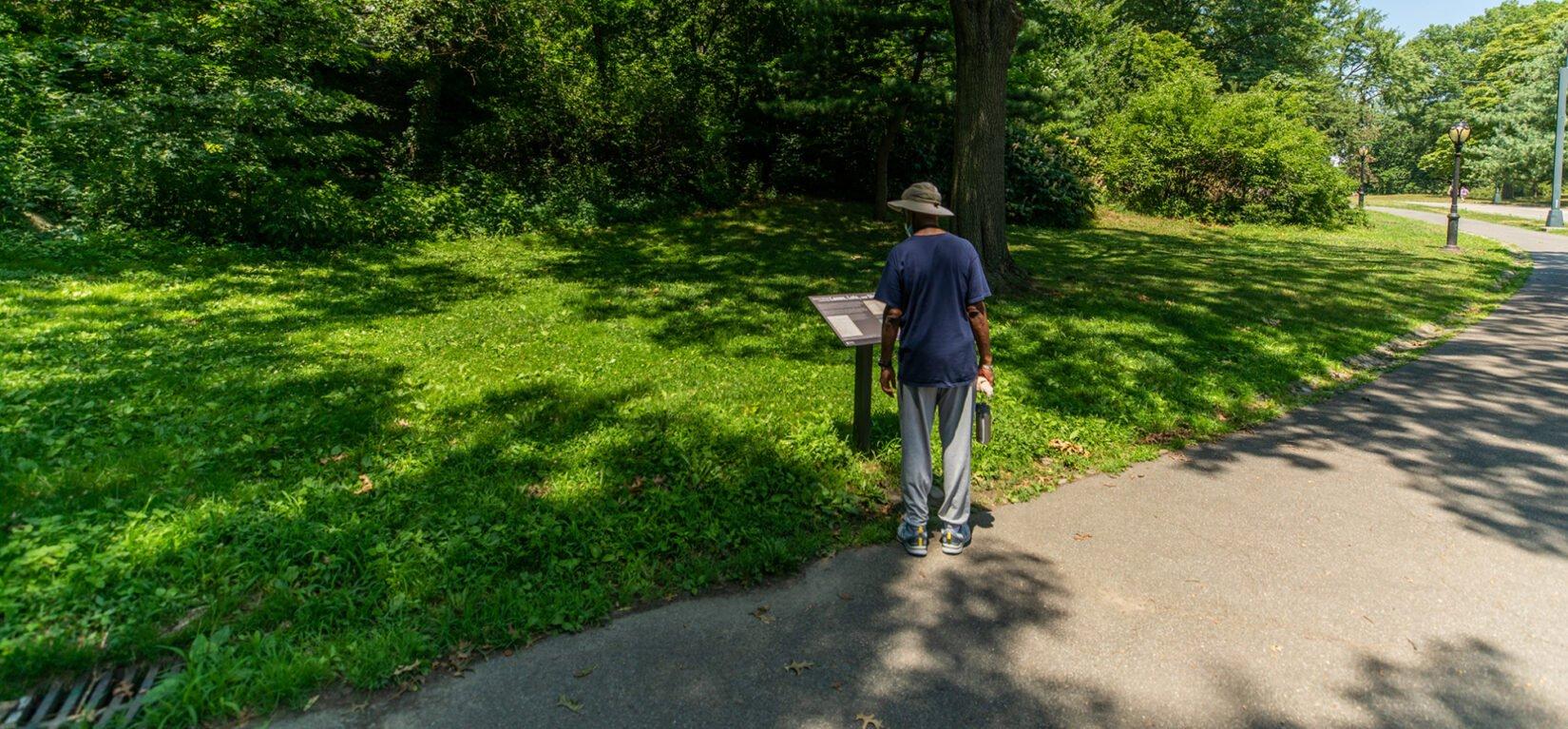 Park visitor reading Discover Seneca Village signage