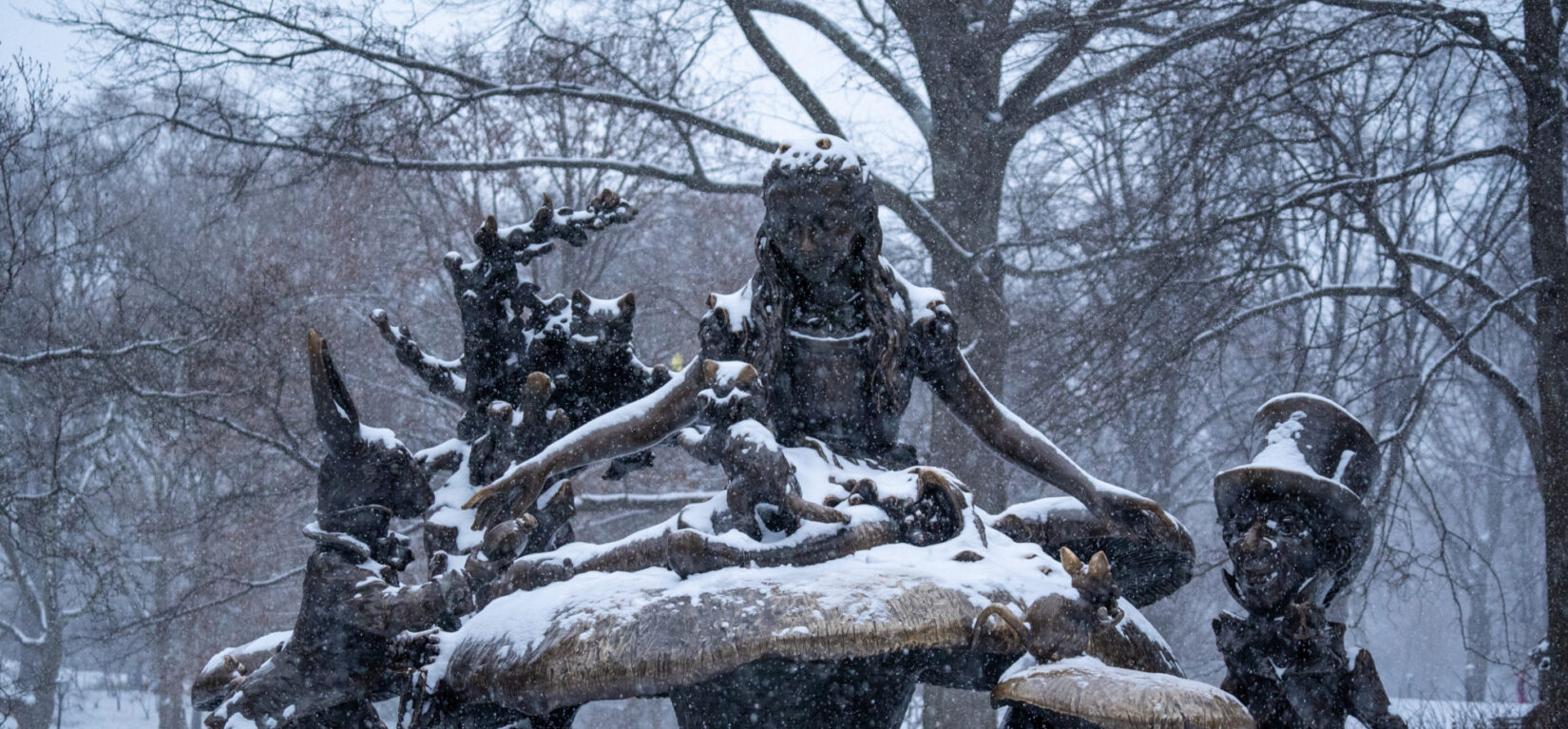 The Alice in Wonderland statue shown dusted with snow