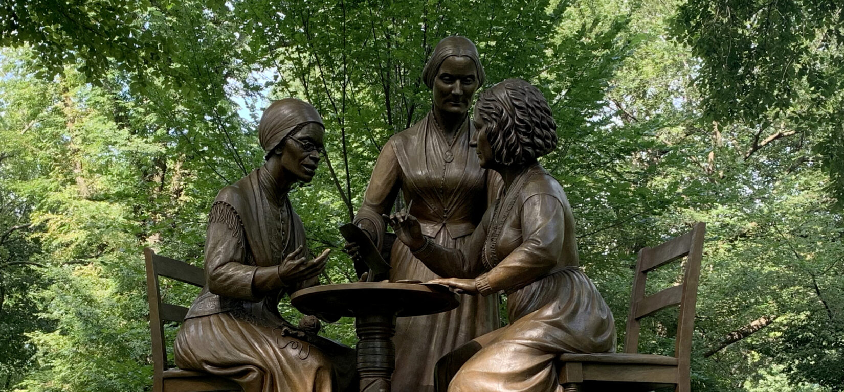 The statue is pictured under the shade of an American Elm with a few flowers left on its base