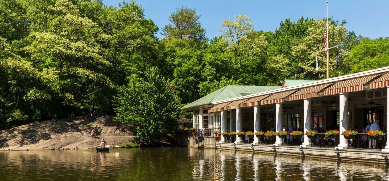 The boathouse is seen reflected in the waters of the Lake.