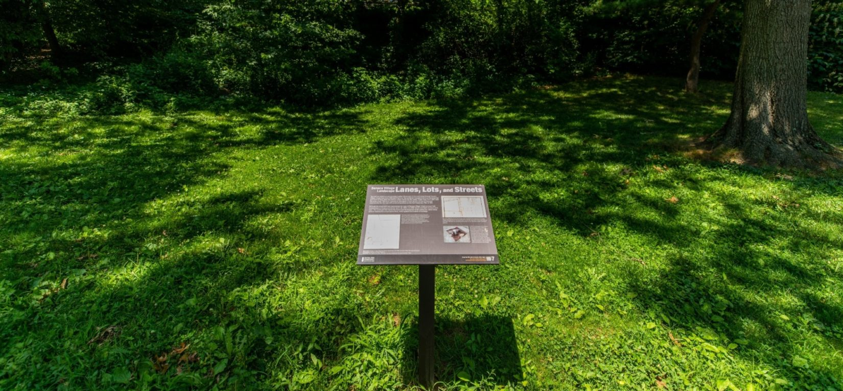 An example of the interpretive signage stands in the landscape of Seneca Village