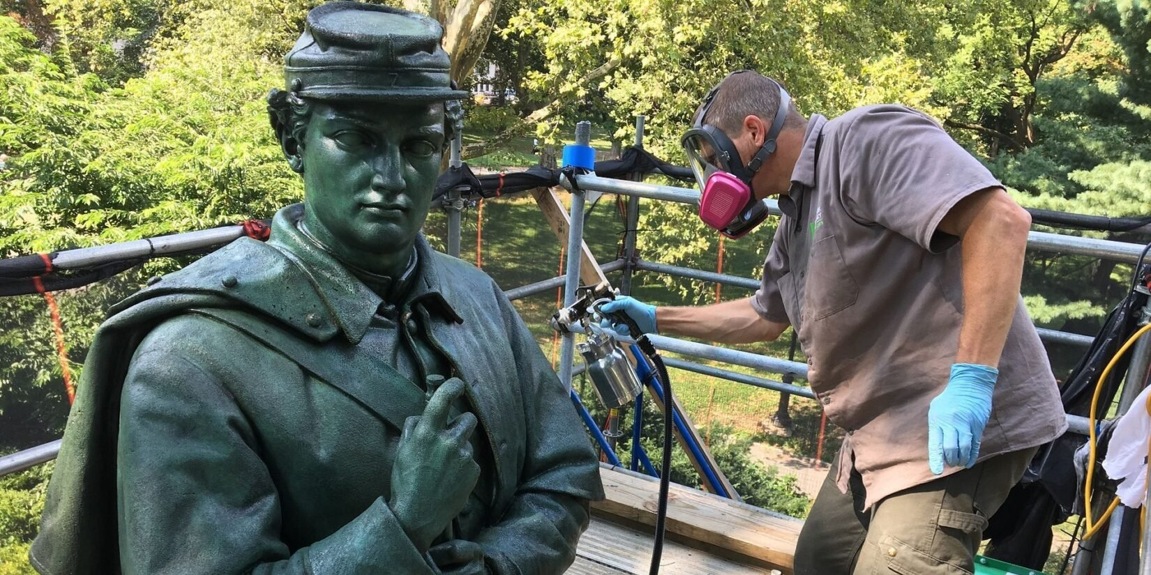 A protective coating is sprayed on the bronze statue by a worker on a scaffold.