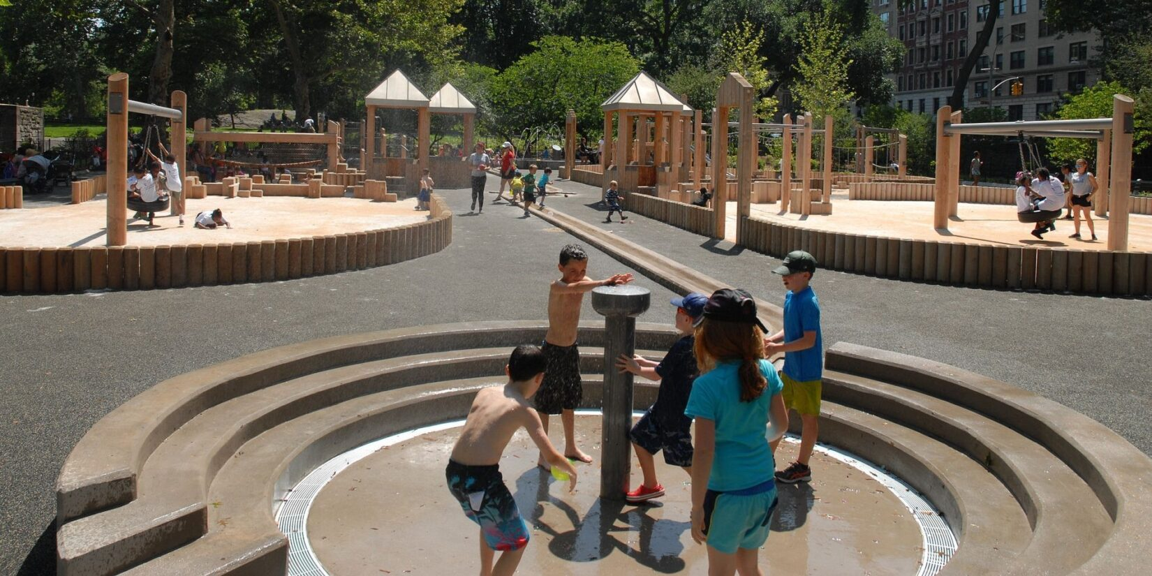 Several children surround the water feature on a cloudless summer day