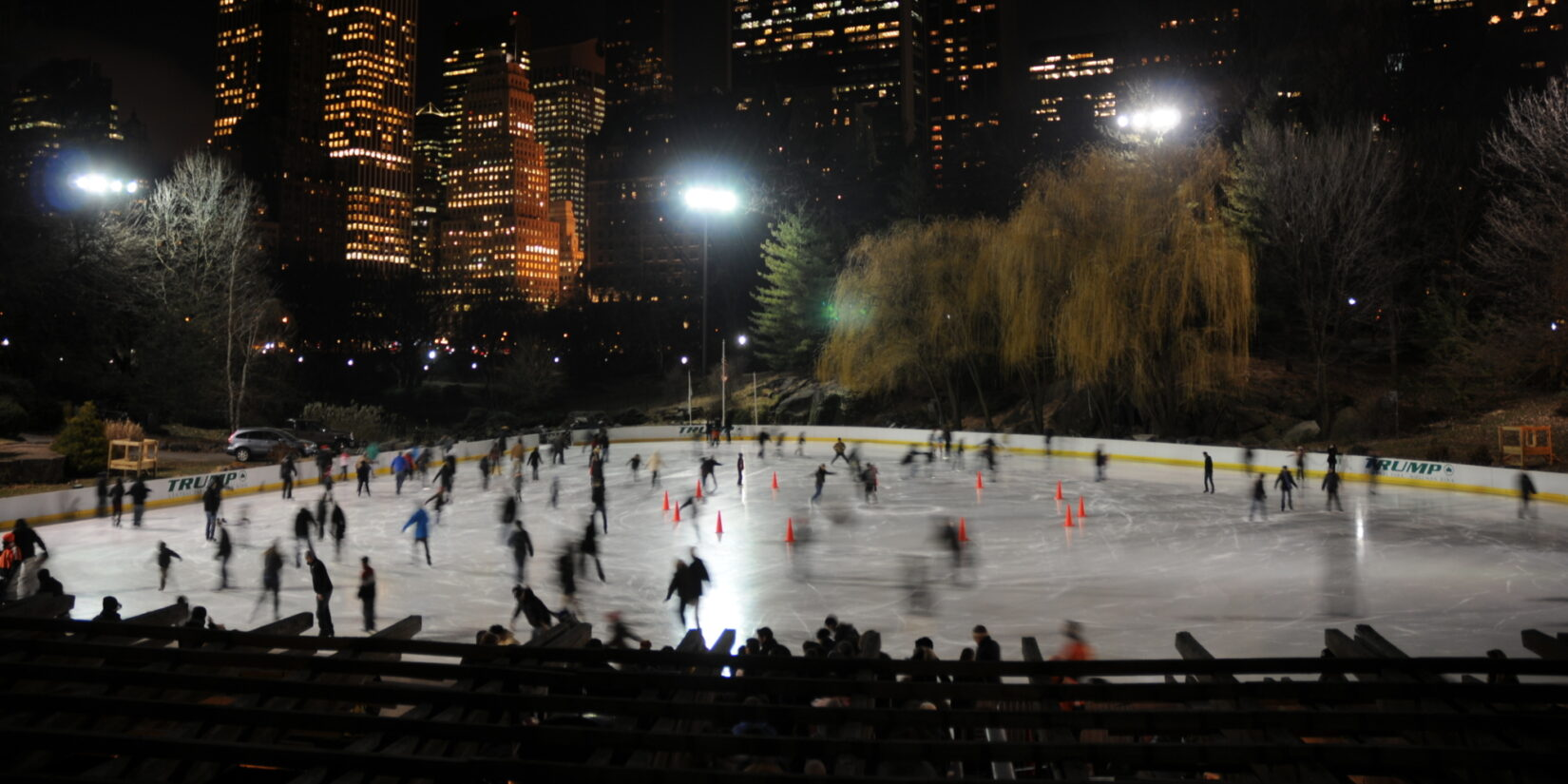 Skaters enjoy the Wollman Rink after dark, with the skyline of Manhattan as a backdrop