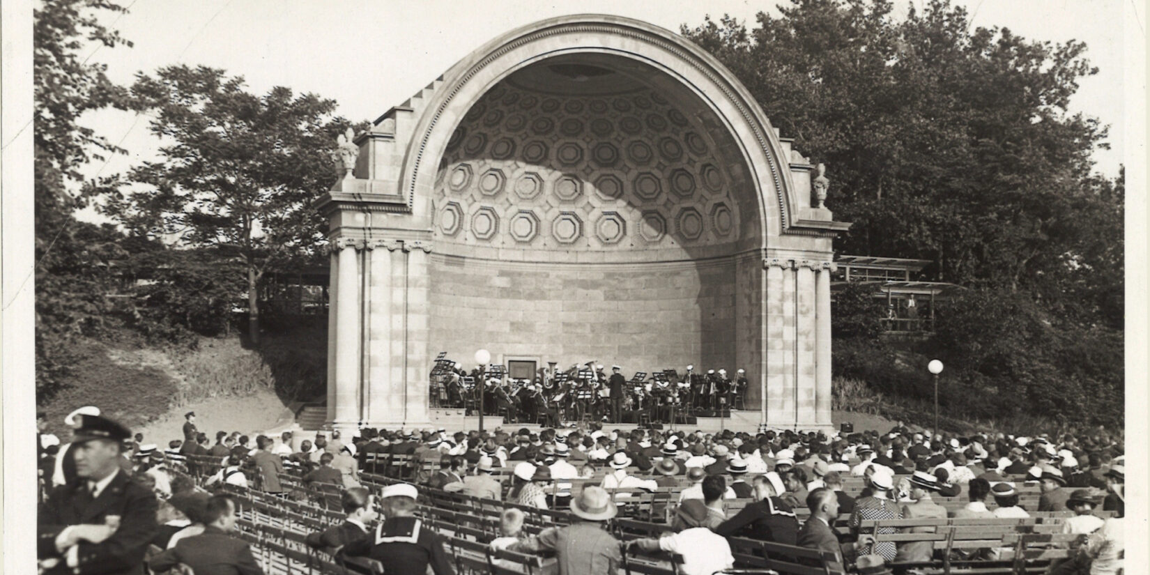 A black-and-white photo of the bandshell hosting a concert.