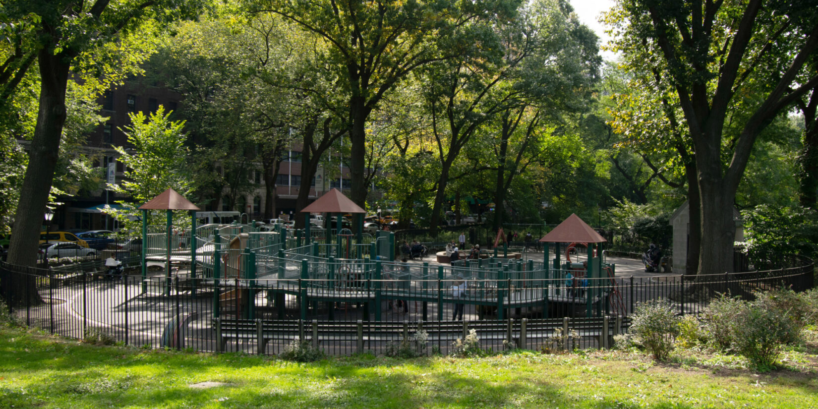 The playground shown in summer, dappled by sunlight