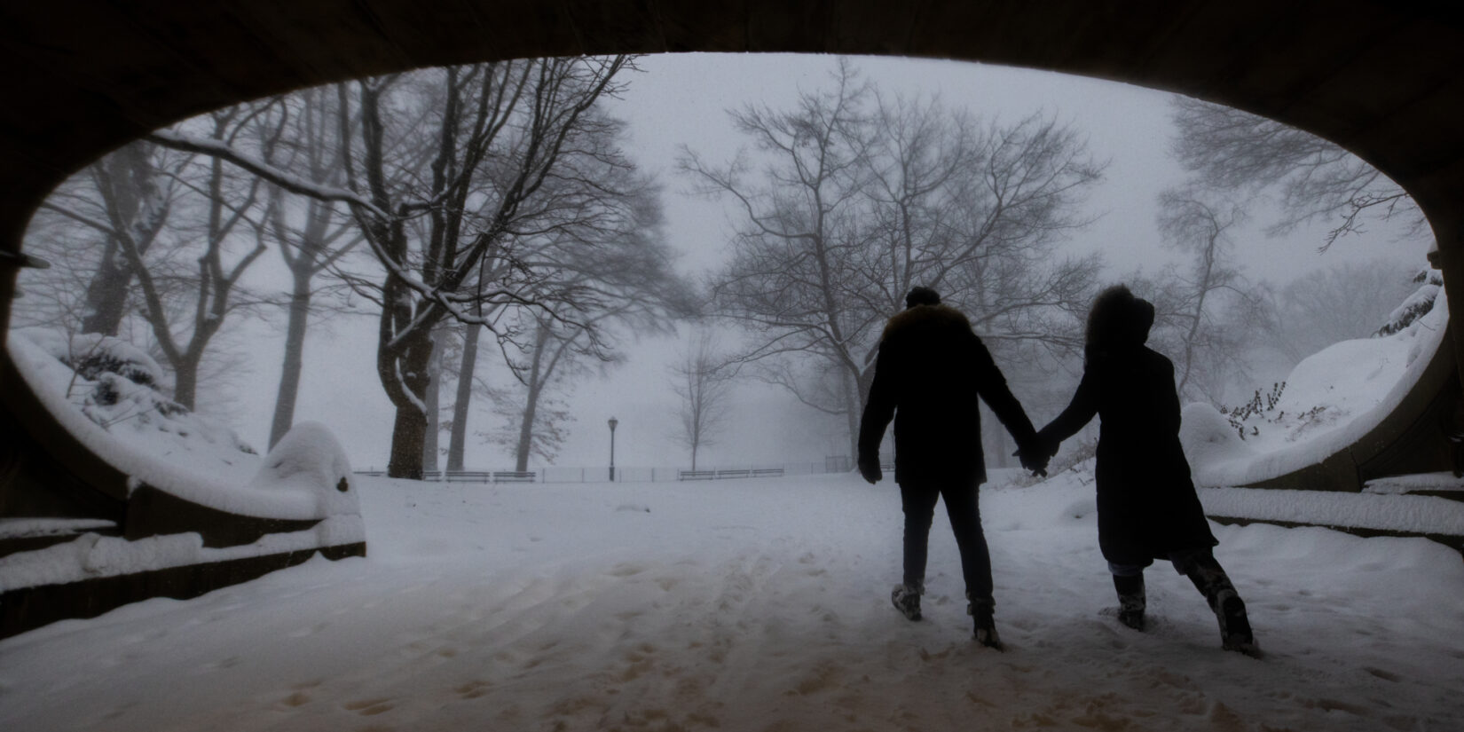 A couple trudge beneath Dalehead Arch in a snowstorm