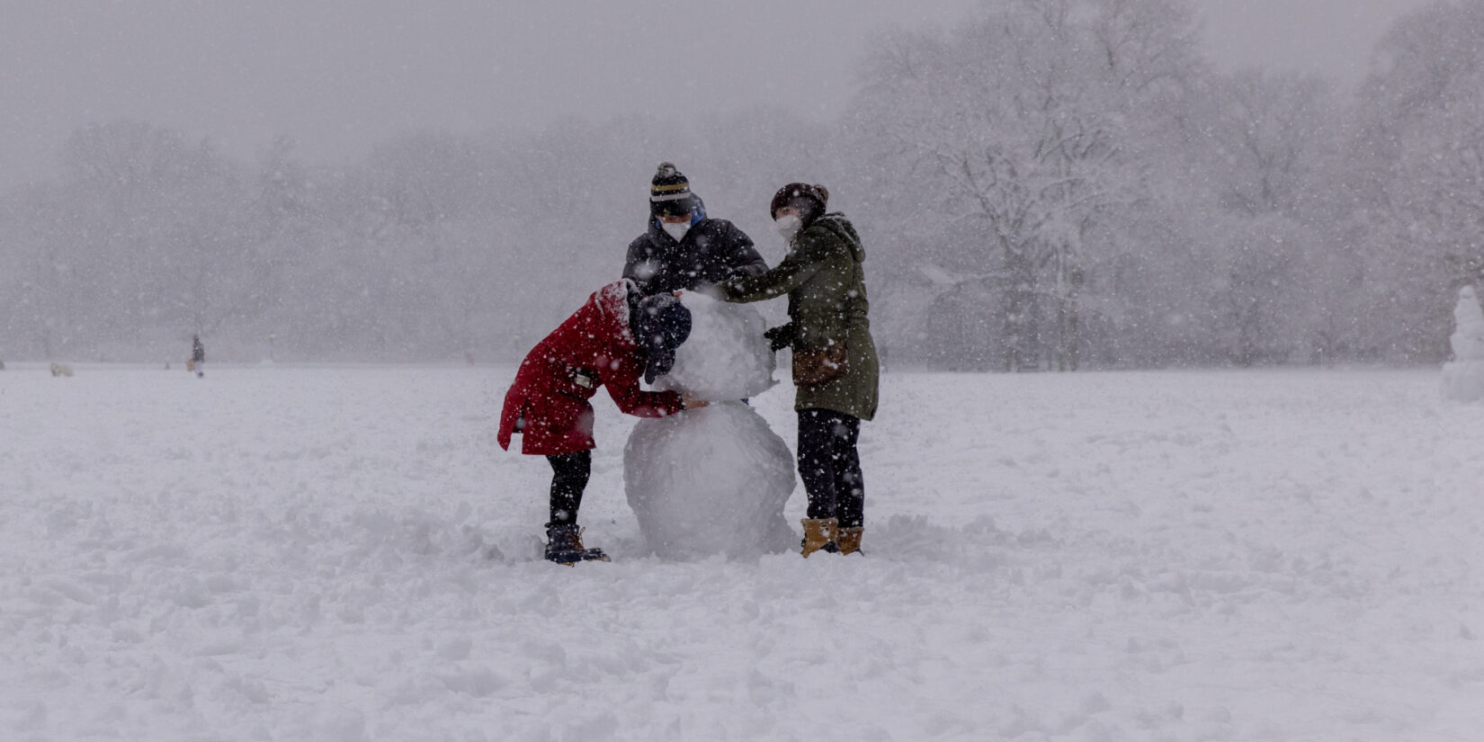 Three parkgoers building a snowman in the middle of a blizzard.