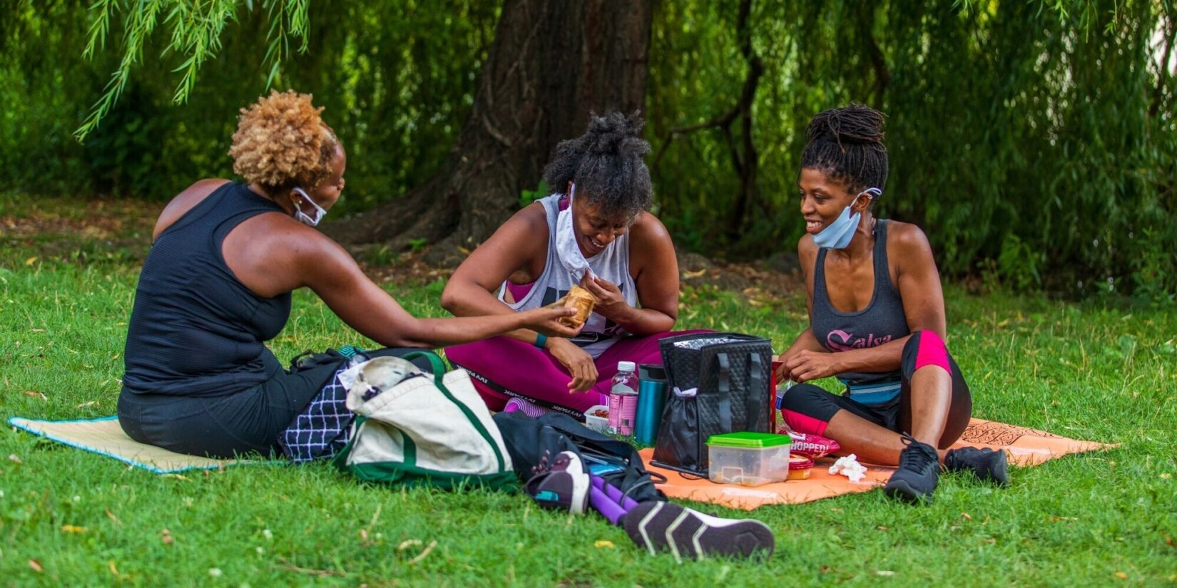 Three women enjoying a picnic on blankets at the Meer.