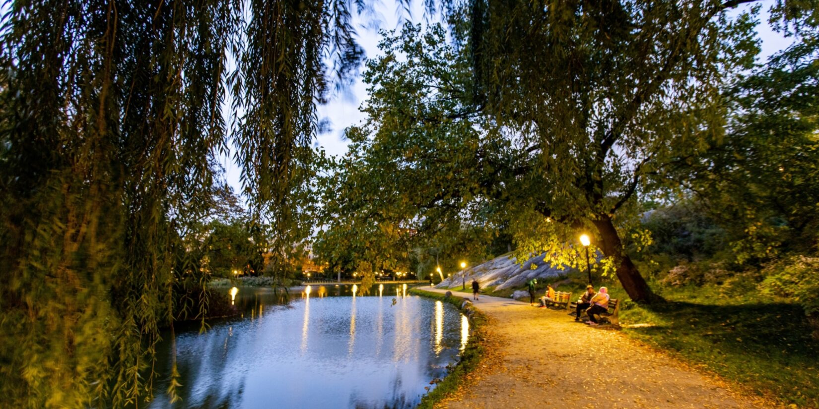A couple sits on a bench on the winding banks of the Harlem Meer in twilight