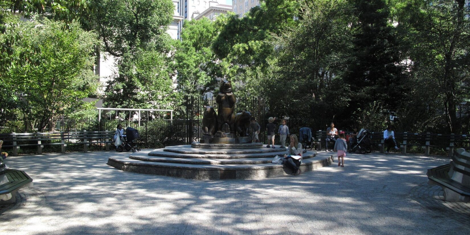 The circular plaza provides bench seating with the statue at the center.