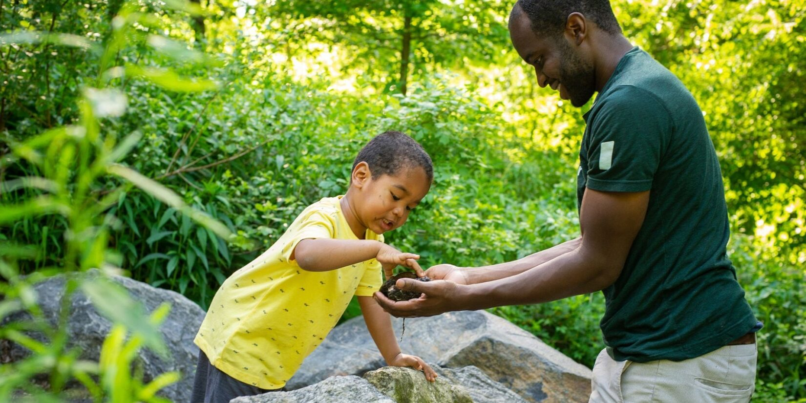 A child pets a turtle being held by a Conservancy guide