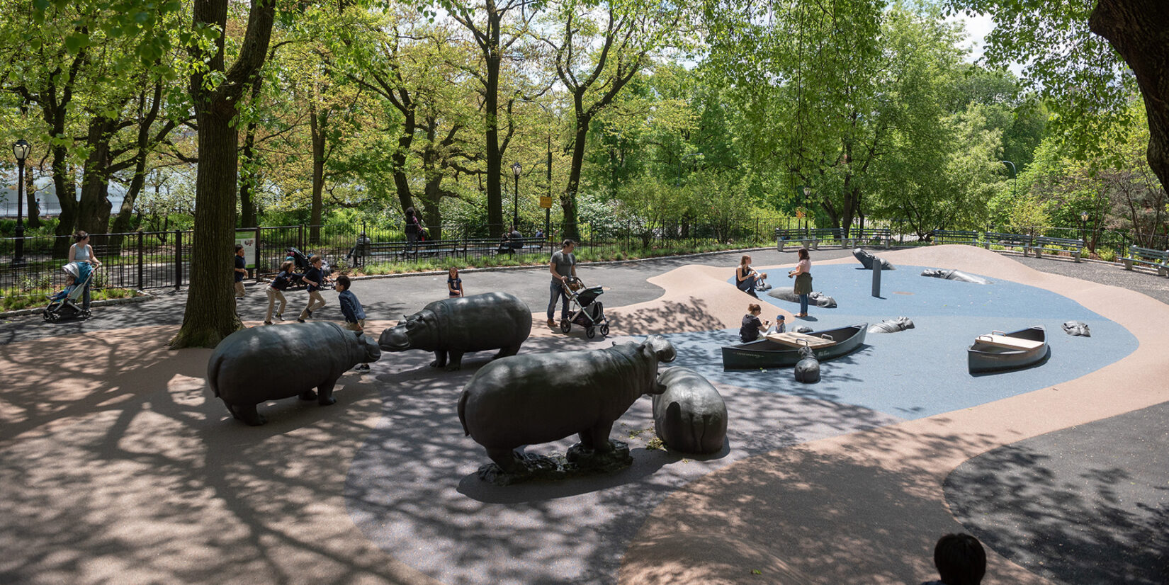 A long view of the playground, with children enjoying the hippos and simulated water area