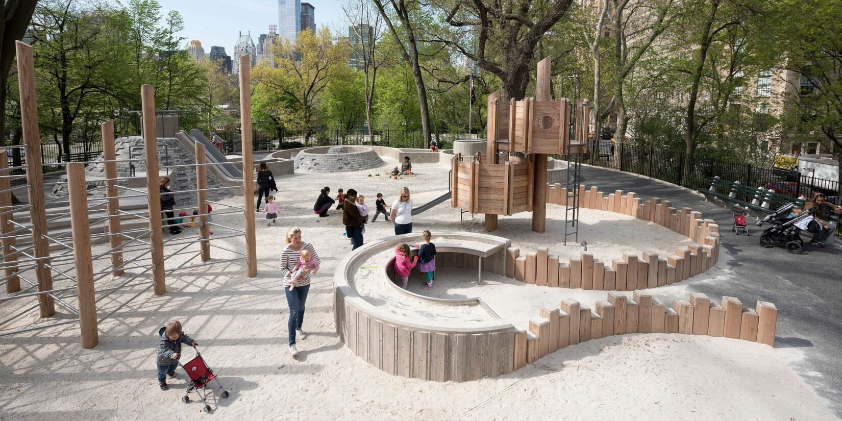 Children and caregivers playing at the sandy end of the playground, in Spring.