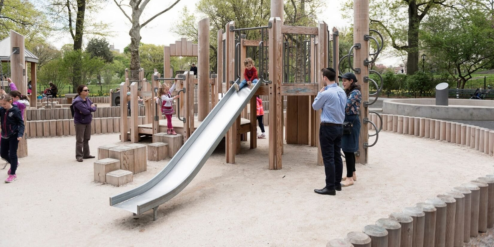 A few parents watch as a toddler prepares to slide down the sliding pond
