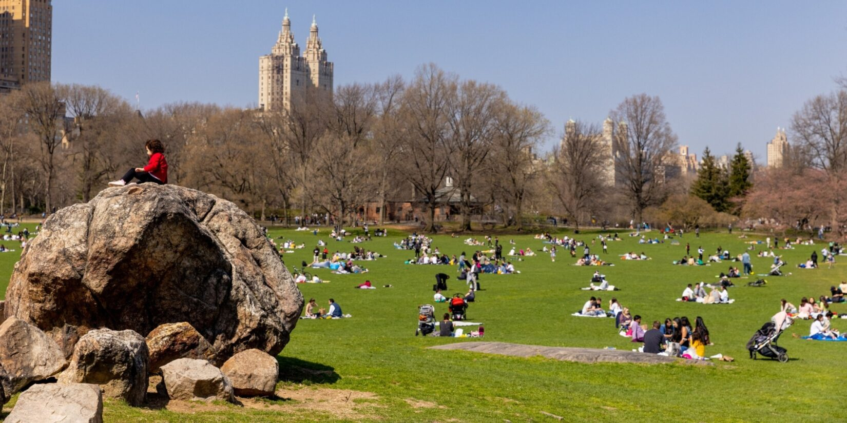 Park-goers on the Sheep Meadow enjoying a crisp Fall day. One visitor sits atop a large boulder.
