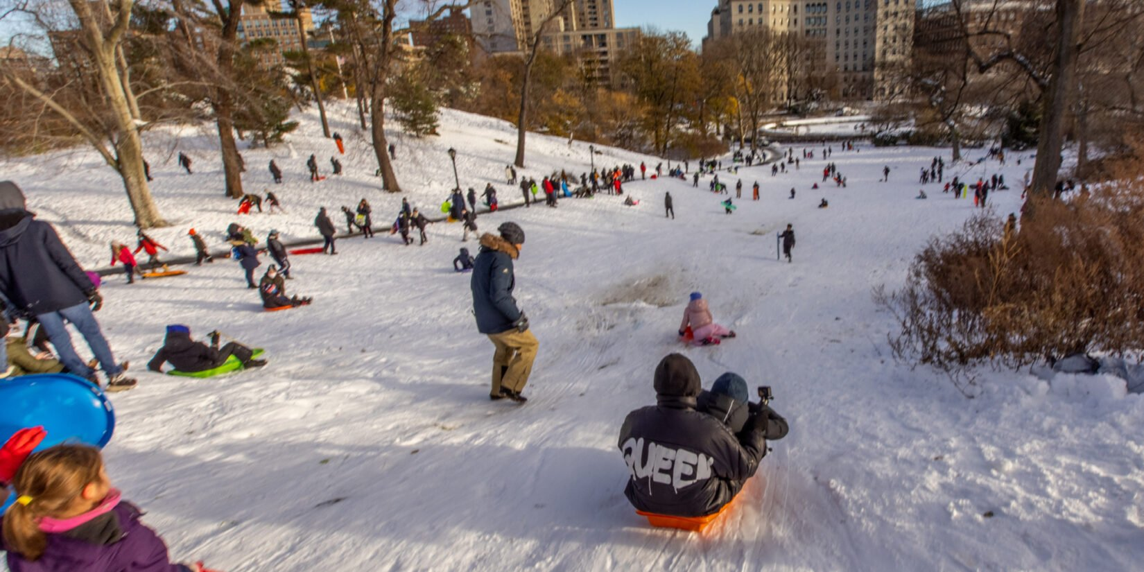 Kids of all ages enjoying sledding under a cold blue sky